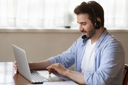 Side view young man wearing wireless headset with microphone, looking at laptop screen, study on online courses. Skilled male teacher giving online educational class to client, working remotely.