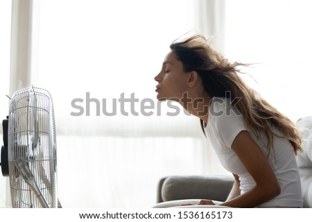 Side view young mixed race woman sitting on couch in front of ventilator indoors. Millennial girl suffering from hot summer weather or high temperature at home, cooling herself with air conditioner.