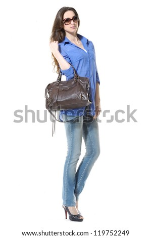 Side view young stylish slim in jeans with handbag posing