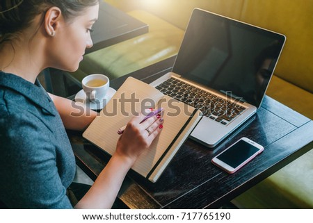 Side view. Young woman sitting at table in cafe in front of laptop, computer and making notes in notebook, diary. Businesswoman working, student studying. Online marketing, education, e-learning. - Shutterstock ID 717765190