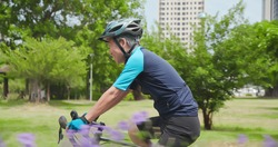 Sideview of asian old man wearing helmet is cycling a bicycle in the park - enjoying sport or hobby living healthy