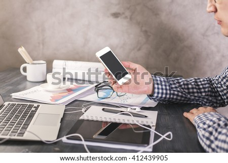 Sideview of male with blank smartphone in hand sitting at office desk with business report and electronic devices #412439905