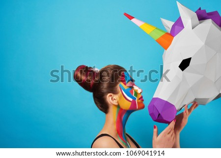 Sideview of pop art portrait of model wearing black opened top. Girl has saturated make up with bright geometrical figures and fancy hairdress. Posing on blue background with pink paper unicorn's head #1069041914