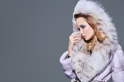 Sideview portrait of a beautiful blonde woman wearing mink and fox fur coat with fluffy hood. Beauty, winter fashion. Copy space.