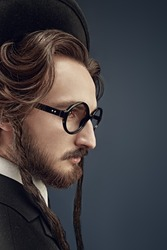 Sideview portrait of a traditional Jewish man with sidedresses, in a black suit and round glasses. Studio shot on a dark blue background.