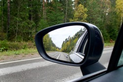 sideview, rearview mirror of a car on road at autumn or summer day at countryside