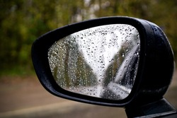 sideview, rearview mirror of a car on road with drops of rain at autumn rainy day '