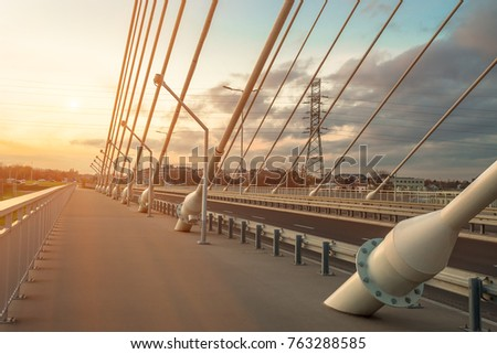 sidewalk and highway going through a cable-stayed bridge with big steel cables, closeup at evening time during a sunset against a background of sky, clouds and sun rays
