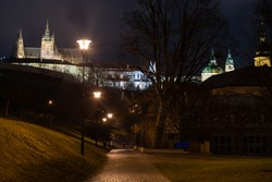 sidewalk and light from street lights in the park and in the background the Cathedral of St. Vitus and Prague Castle at night in Prague