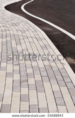 Sidewalk and street curve detail, stone patterns leading the way