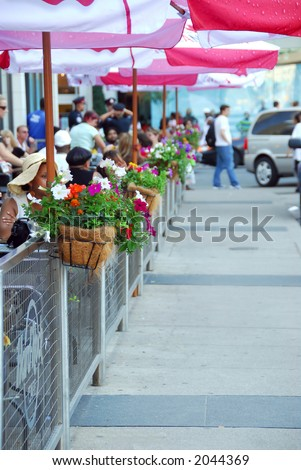 Sidewalk cafe behind a fence decorated with flowers full of people