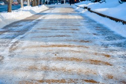 Sidewalk covered with sand and salt mixtures. Prevent slips on ice in city. Salt and sand melt ice on roads and walkways. Deicing chemicals on pavement. Prevent slipping on road with deicing reagents