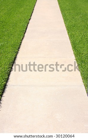 Sidewalk passage in green grass