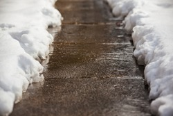 Sidewalk shoveled after a snowfall in winter