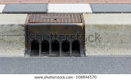 Sidewalk with a street drainage and road