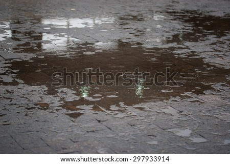 Sidewalk with puddles of water and raindrops