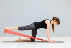 Sideways of sporty European woman has workout with rubber red band, dressed in black sportsclothes, has exercises for buttocks, poses on knees at yoga mat against grey background. Motivation concept.
