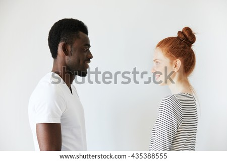Sideways portrait of a happy couple staring at each other in white morning room. Afro Amercian man in white shirt and redhead girl in stripped longsleeve smiling, showing positive emotions and joy. - Shutterstock ID 435388555