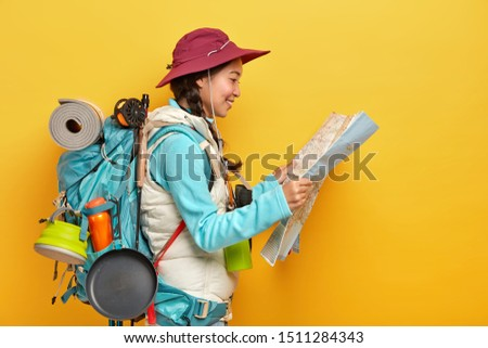 Sideways shot of Asian female tourist studies map, finds new destination to explore, travels alone, wears cap and active wear, carries big rucksack with necessary things for travel, isolated on yellow