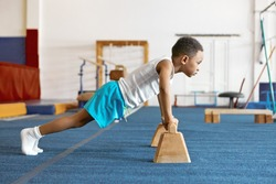 Sideways shot of concentrated serious Afro American kid in sports clothes keeping feet on floor and hands on wooden bar, doing push ups. Strong self determined black boy planking at fitness center