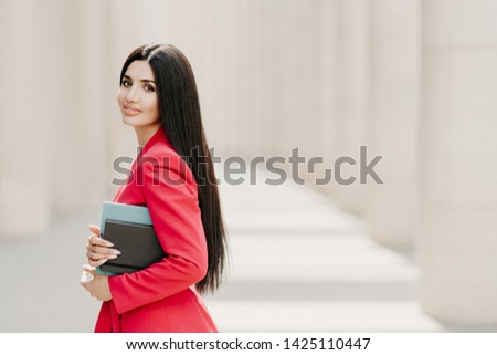 Photo of Sideways shot of elegant brunette lady with dark long straight hair, dressed in fashionable red suit, has manicure, carries diary, stands outdoor over white building. Female employee in formal apparel