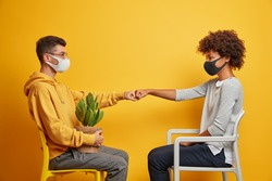 Sideways shot of interracial woman and man sit on chair opposite each other make fists bumps wear face masks dressed casually isolated on yellow background. Couple protecting themselves from pandemic