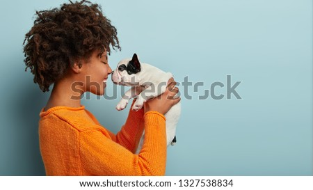 Sideways shot of pleased charming young woman has dark skin, curly hairstyle, touches noses with favourite dog, plays with french bulldog, dressed in orange jumper, isolated over blue background. #1327538834