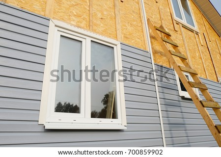 siding covering the wall of a house under construction - Shutterstock ID 700859902
