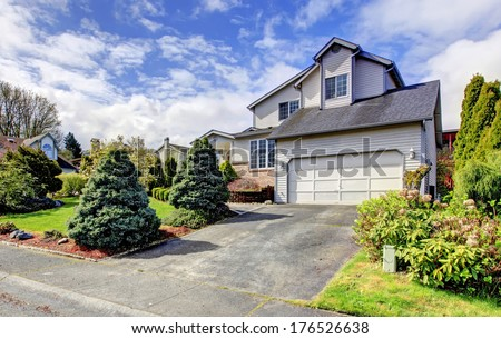 Siding house with garage. Green lawn with trimmed hedges, flourishing bushes and fir trees.