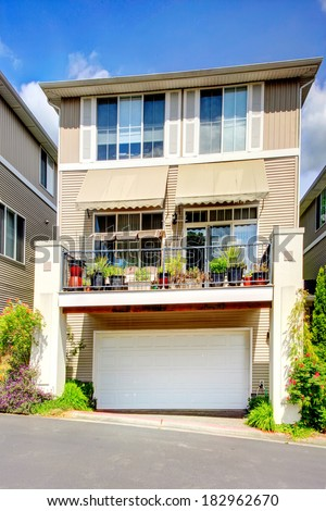 Siding residential building with balcony and garage