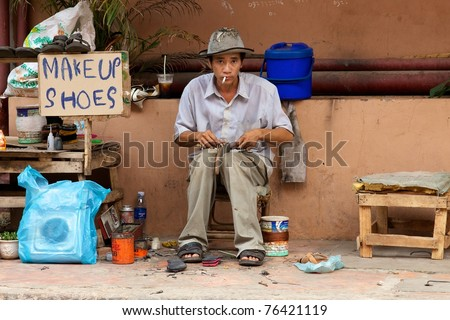 SIEM REAP, CAMBODIA- APRIL 1: Street Vendor offering shoe repair in Siem Reap on April 1, 2011. Cambodia's population is 14,701,717 and the Median age in Cambodia is 23 years old.