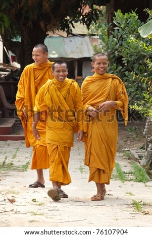 SIEM REAP, CAMBODIA- APRIL 1: Three unidentified Buddhist monks walking in Siem Reap on April 1, 2011.  Buddhism is currently estimated to be the faith of 96% of the Cambodian population.
