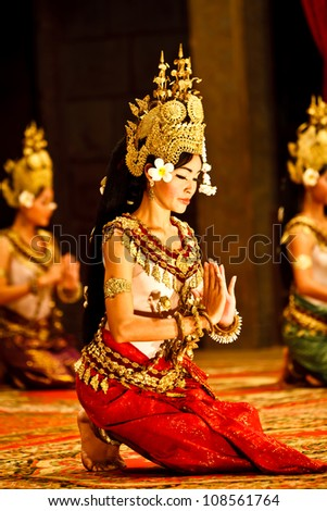 SIEM REAP, CAMBODIA - DECEMBER 28, 2008: 3 kneeling Khmer classical dancers performing in traditional costume December 28, 2008 in Siem Reap, Cambodia.Angkor Wat is the most visited place in Cambodia.