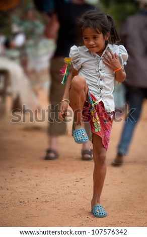 SIEM REAP, CAMBODIA - DECEMBER 28: Unidentified girl plays with a kick toy at market in Angkor Wat, UNESCO World Heritage site most visited on December 28, 2008 in Siem Reap, Cambodia.