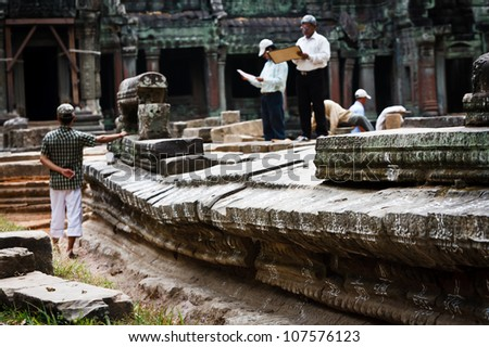 SIEM REAP, CAMBODIA - DECEMBER 26: Unidentified men preserving and restoring temples at most visited UNESCO world heritage site, Angkor Wat, on December 26, 2008 in Siem Reap, Cambodia.