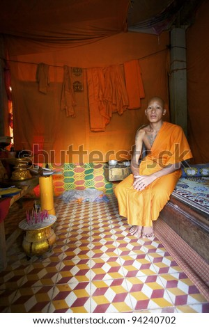 SIEM REAP, CAMBODIA - JAN 22: Buddhist monk sitting in his room at Wat Atwea in Siem Reap on January 22, 2012. Buddhism is currently estimated to be the faith of 96% of the Cambodian population.