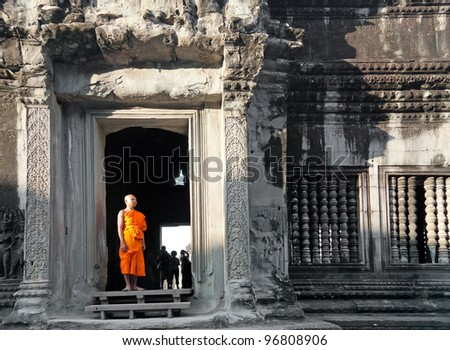 SIEM REAP, CAMBODIA - JANUARY 07: Monk posing in Angkor Wat temple, January 07, 2012, Siem Reap, Cambodia. Buddhism is currently estimated to be the faith of 96% of the Cambodian population. - stock photo