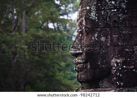 SIEM REAP, CAMBODIA: Profile of Prasat Bayon temple complex statue against jungle background. - stock photo