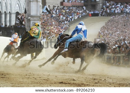 "SIENA, ITALY - AUGUST 16: Unidentified riders compete in the horse race ""Palio di Siena"" in the medieval square ""Piazza del Campo"" on August 16, 2007 in Siena, Italy. The race is held twice every year."
