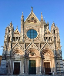 SIENA, ITALY. Date of photo is 27.09.2015. Siena Cathedral. Main entrance view, green door capped with bronze sun, pink marble facade, light, decoration. Mosaic. Duomo di Siena.