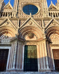 SIENA, ITALY. Fragment of Siena Cathedral. Main entrance, green door capped with bronze sun, pink marble facade, light, decoration Date of photo is 27.09.2015
