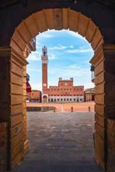 Siena, Piazza del Campo square, Torre del Mangia tower and Palazzo Pubblico building. Arch as a frame. Tuscany, Italy.