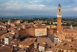 Siena, Tuscany, Italy. View of the Old Town - Piazza del Campo, Palazzo Pubblico di Siena, Torre del Mangia at sunset from Siena Cathedral (Duomo di Siena) .