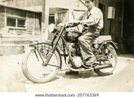 SIERADZ, POLAND, CIRCA FIFTIES - Vintage portrait of man on motorcycle