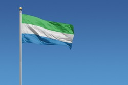 Sierra Leone flag in front of a clear blue sky