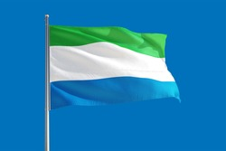 Sierra Leone national flag waving in the wind on a deep blue sky. High quality fabric. International relations concept.