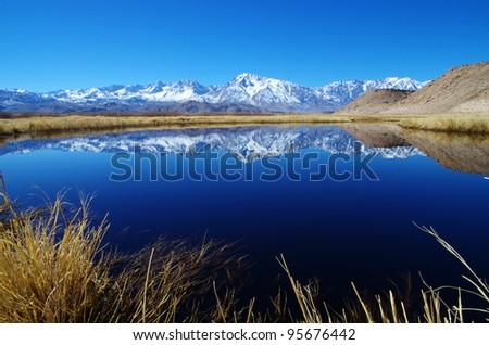 Sierra Mountain reflection in an oxbow of the Owens River with foreground grasses
