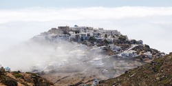 Sifnos island, Kastro ancient village Cyclades Greece. On top of hill through fog are build whitewashed traditional stonewall houses church streets that drives to heaven. Cloudy day Greek destination.