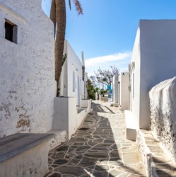 Sifnos island, Kastro village, Cyclades Greece. Sunny day exploration between traditional whitewashed stonewall buildings empty historic narrow cobblestone alley. Destination summer resort vacation.