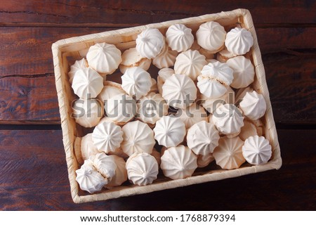 sigh or homemade meringue is a sweet made from egg whites, sugar and lemon in the basket on wooden table Foto d'archivio ©